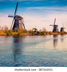 Sunny spring scene in the canal in Netherlands. Dutch windmills at Kinderdijk, an UNESCO world heritage site. Tipical Holland landscape.