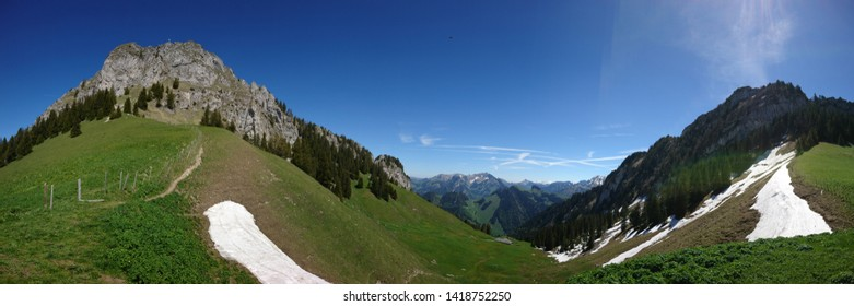 Sunny Springtime panorama of Alpine peaks at col des Combes in Canton Fribourg in Switzerland with two craggy peaks : Dent de Broc and Dent de Chamois