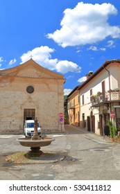 Sunny square with old fountain in front of a church in Norcia, region of Umbria, Italy