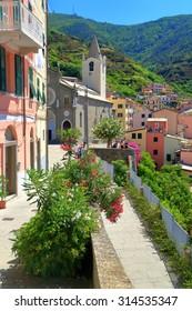 Sunny street leading to the church of San Giovanni Battista in Riomaggiore, Cinque Terre, Italy