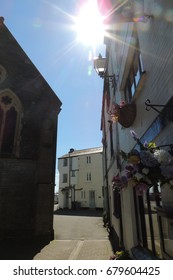 A sunny street in Looe in Cornwall, with a church and white walled buildings