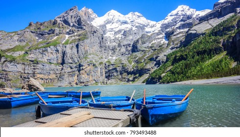 Sunny Summer Activities and recreation, rowing blue boats while enjoying beautiful Swiss alps view on Lake Oeschinen (Oeschinensee), near Kandersteg, Bernese Oberland, Switzerland, Europe
