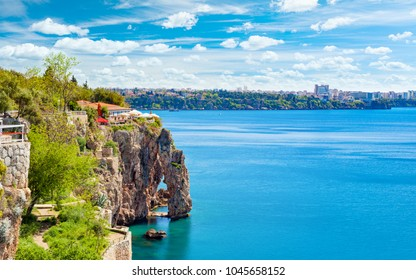 Sunny summer day with blue sky and clear sea in Antalya. Rocky shore, terrace with cafes and city slyline on horizon in popular seaside resort city Antalya, Turkey