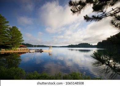 Sunny summer day in Canada. Adirondack and lounge chairs sitting on a wooden dock facing a calm lake. Sailing boats are tied to the dock.