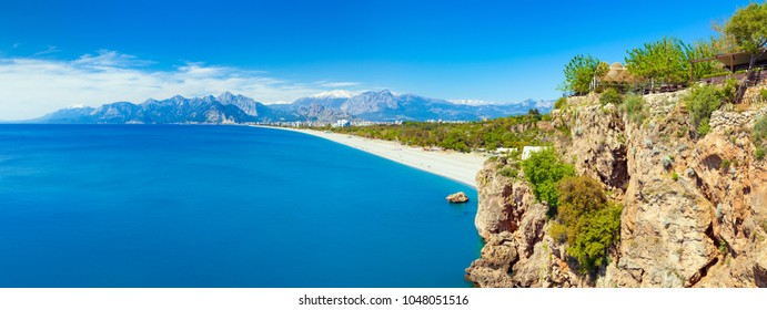 Sunny summer day with clear blue sky in Antalya. Panoramic view of beautiful blue gulf and Konyaalti beach in popular resort city Antalya, Turkey.