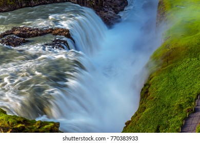 Sunny summer day. Huge masses of water crash into the abyss. The most picturesque waterfall in Iceland - Gullfoss. The concept of extreme and phototourism