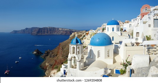 Sunny summer day in Oia, Santorini. Traditional churches with blue domes.