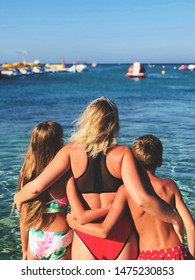 Sunny summer day on Cyprus, mother and children are staying back in the clear blue water.
