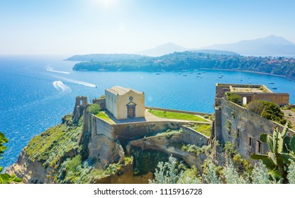Sunny summer day in Procida, Italy. Aerial view of Santa Margherita Nuova monastery situated on Punta dei Monaci, blue lagoon near Procida Island, Naples, Italy.