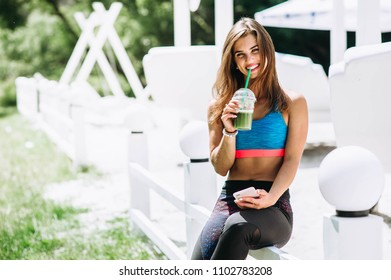 Sunny summer day young woman athletes in sports clothes are sitting on bench relax after sports with phone and sport drink