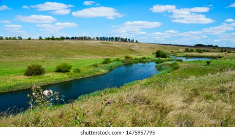 Sunny summer landscape with river and beautiful view of fields,meadows,pastures and woods.