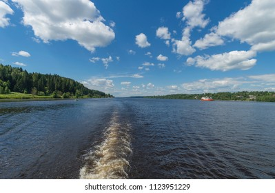 Sunny summer landscape with river. Green hills, fields and meadows. River Volga in Russia. Day. Calm. Warm sunlight. Cloudless clear blue sky.