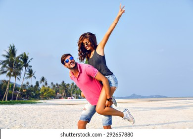 Sunny summer portrait of happy amazing beautiful couple, having fun at lonely tropical beach enjoy their vacation, trendy hipster clothes and vintage sunglasses, joy, happiness, love, relations.