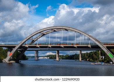 Sunny summer view of a arched concrete train bridge with sky, water and boats.