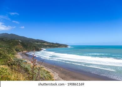 Sunny summer view of Ngarunui surfers beach, near Raglan, Waikato, New Zealand