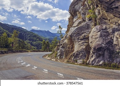 Sunny summer view with steep rocky cliff on the side of a road crossing the Siriu mountains in Buzau county, Romania.
