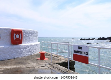 Sunny summery image of a sea wall painted white with a bright red bollard. A red life preserver and a No Swimming sign. The sunlight sparkles on the sea behind. Focus is the no swimming sign.