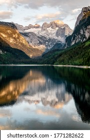 Sunny sunset colorful summer alpine view. Peaceful mountain lake with clear transparent water and reflections. Gosauseen or Vorderer Gosausee lake Salzkammergut Upper Austria. Dachstein summit glacier