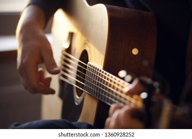 Sunny sunset light illuminates the hands of the guitarist, playing a melody on a wooden six-string acoustic guitar