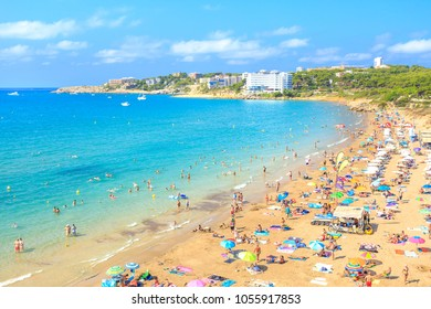 Sunny tropical resort coastline. Beautiful sand beach and blue sea water under clear sky. Beach full of tourists.