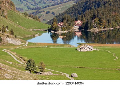 Sunny views of pastures, Seealpsee Inn, Forelle Inn from Oberstofel by Seealpsee lake in Alpstein, Appenzell Alps, Switzerland