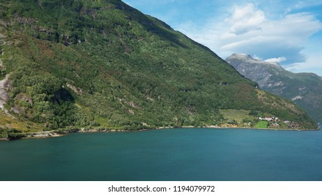 Sunny views of the surrounding steep cliffs and pristine glacier fjord water at ESCO-protected Geiranger fjord, one of Norway's most popular natural attractions, Geiranger, Norway