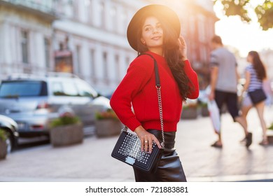 Sunny warm fashionable portrait of slim attractive stylish girl in red pullover walking in sunny city .