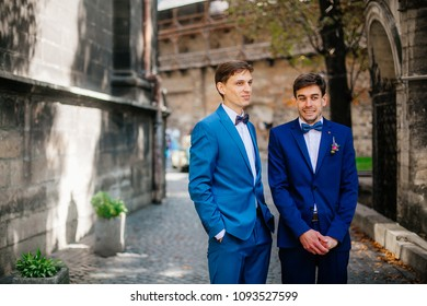 Sunny wedding day. Groom and bestman groomsmen dancing and having fun around after wedding ceremony in the old city street.