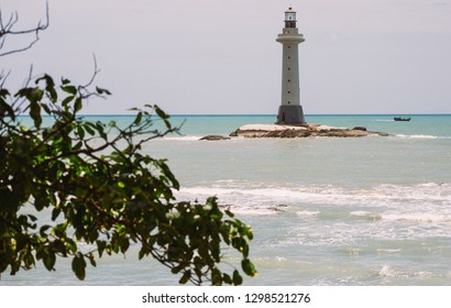 Sunny white sand beach with palm. Relax travel and holiday. Lighthouse at seashore. Ocean coast.