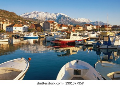 Sunny winter day. Fishing boats in harbor in Mediterranean town at foot of snowy mountains. Montenegro, Bay of Kotor. View of Marina Kalimanj in Tivat city and snow-capped of Lovcen mountain