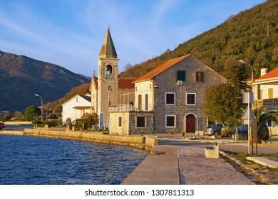 Sunny winter day in Mediterranean village. Montenegro, Tivat.  View of Donja Lastva village and Catholic Church of Saint Roch