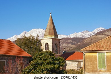 Sunny winter day in Mediterranean village. Red tiled roofs  and bell tower against blue sky and snow-capped mountain. Montenegro, Tivat, Donja Lastva village, Catholic Church of Saint Roch