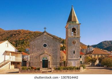 Sunny winter day in Mediterranean village. Montenegro, Tivat. Catholic Church of Saint Roch in Donja Lastva village