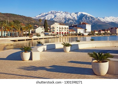 Sunny winter day. Montenegro, Bay of Kotor. View of embankment of Tivat city and snowy peaks of Lovcen mountains