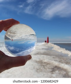 Sunny winter day on the pier in Grand Haven Michigan,looking thru a lens ball at the lighthouse
