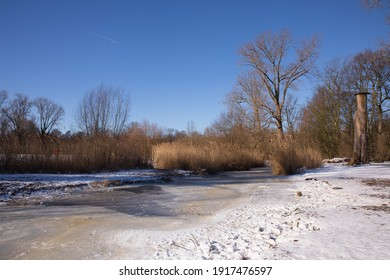 Sunny winter day with snow and frozen canal and lake in the Vondelpark in Amsterdam, the Netherlands
