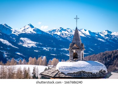 Sunny winter landscape with wooden roof and cross at Ski Area in Dolomites, Italy - Alpe Lusia. Ski resort in val di Fassa near Moena