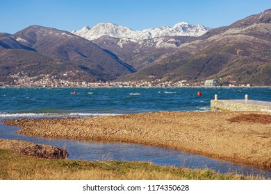 Sunny winter Mediterranean landscape with blue bay, yellow beach and snow-capped mountains. Montenegro, view of Bay of Kotor (Adriatic Sea) near Tivat city