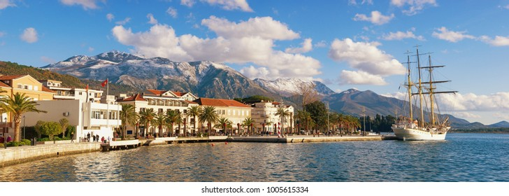 Sunny winter in Mediterranean town. Panoramic view of the embankment of Tivat city and snow-capped Lovcen mountain, Montenegro