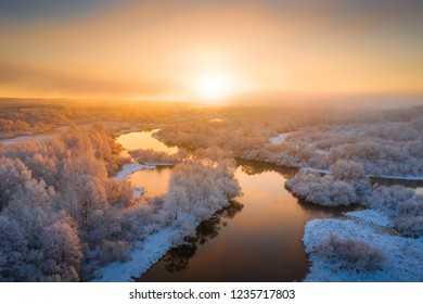 Sunny winter morning. Beautiful winter landscape with river and fog. White trees covered with frost are illuminated by a bright rising sun. Colorful winter natural background.