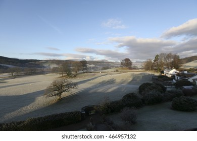 An sunny,frosty, early morning view over fields and woodland to Esthwaite Water