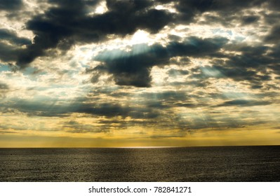 Sunrays behind the clouds shining on the sea