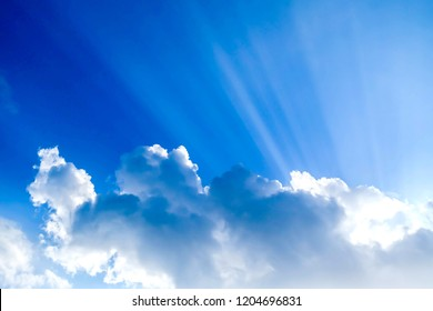 Sunrays in blue sky with white clouds
