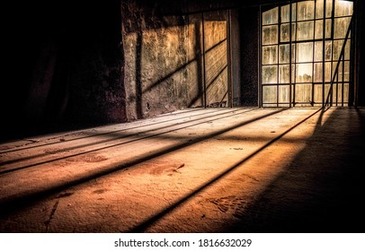 Sunrays fall into the old room through the dusty window