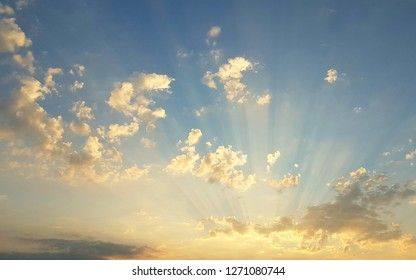 sunrays hitting golden clouds in stunning blue sky