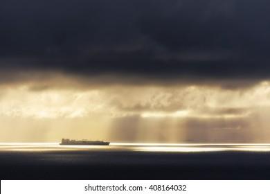 sunrays on the ocean with a cargo ship