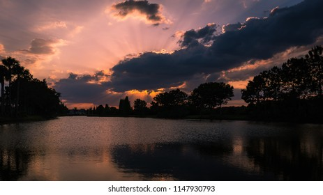 Sunrays peaking out behind storm clouds on a beautiful Brandon Florida sunset.