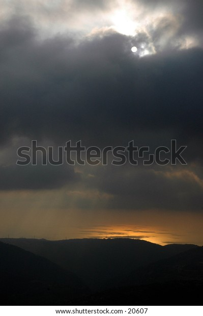 sunrays penetrating the clouds to illuminate parts of the sea