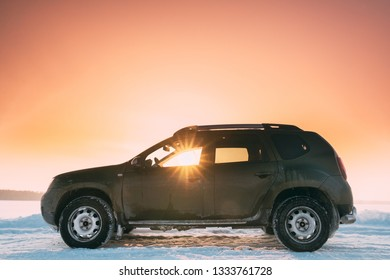 Sunrays Through Window Of Car Renault Duster Or Dacia Duster Suv Parked On Winter Snowy Field At Sunset Dawn Sunrise.