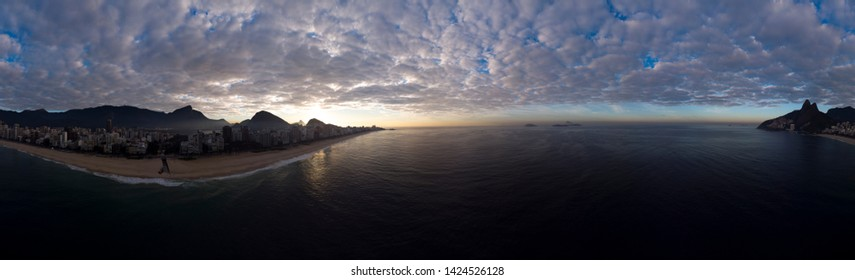Sunrise 360 degree full panoramic aerial view of Rio de Janeiro with Ipanema beach in the foreground and the wider cityscape in the background with clouds lit up by the sun from below